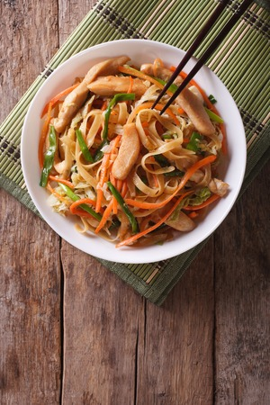 china cuisine: Chinese fried noodles with chicken and vegetables. vertical top view Stock Photo