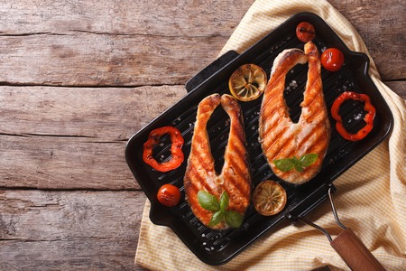 Salmon steak with vegetables on a grill pan. horizontal view from above Foto de archivo