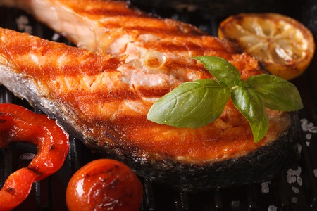 cherry tomato: Grilled red fish steak salmon macro and vegetables on the grill. horizontal