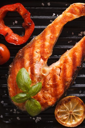 grilled food: Grilled red fish steak salmon and vegetables on the grill pan. vertical top view close-up