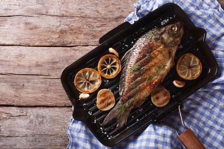 pescado frito: La carpa a la plancha con lim�n en una cacerola de la parrilla, vista horizontal desde arriba