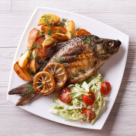 grilled fish with fried potatoes and salad on a plate. top view closeup