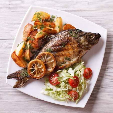 pescado frito: pescado a la parrilla con papas fritas y ensalada en un plato. arriba vista de cerca
