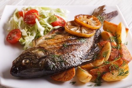 cooked fish: fried fish carp with potato and salad on a plate close-up. horizontal Stock Photo