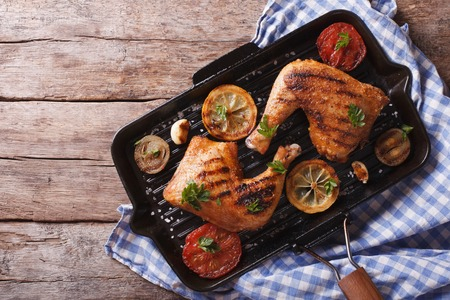 pans: Grilled chicken leg and vegetables on the grill pan. horizontal view from above, rustic style Stock Photo