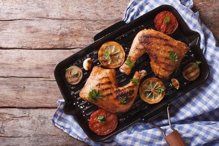 pollo frito: Pierna de pollo a la plancha y verduras en la sartén. visión horizontal de estilo rústico anterior