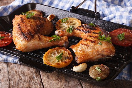 hot legs: Chicken legs grilled on a grill pan close-up. horizontal, rustic style