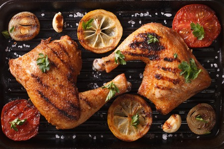 Two grilled chicken legs and vegetables on the grill pan close-up. horizontal view from above