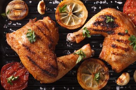 aves de corral: Dos piernas de pollo y verduras a la parrilla en la macro cacerola de la parrilla. visión horizontal desde arriba Foto de archivo
