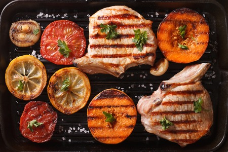 steak grill: Grilled pork and autumn vegetables on a grill pan. top view horizontal macro