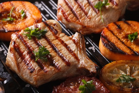 roast pork: Grilled pork steak and pumpkin on a grill. Horizontal macro, rustic style