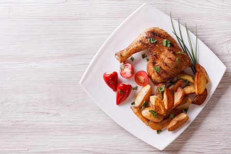 Grilled chicken leg and roasted potatoes on a plate. horizontal view from above