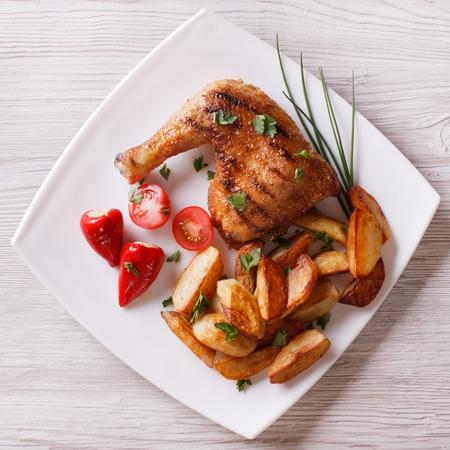 Muslos de pollo a la plancha y patatas asadas en un plato. vista desde arriba Foto de archivo - 39556649