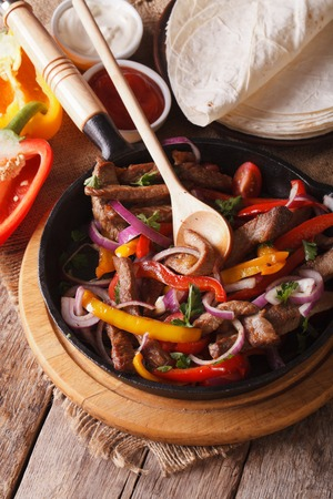 Fajitas close up and ingredients on the table. vertical view above, rustic style