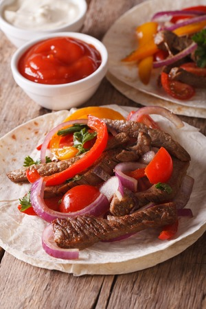 ethnic food: Mexican food: tacos with meat and vegetables close-up. Vertical, rustic style