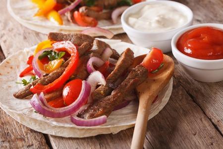 tortilla de maiz: Tortilla con carne y verduras en primer plano en la mesa. Estilo r�stico Horizontal