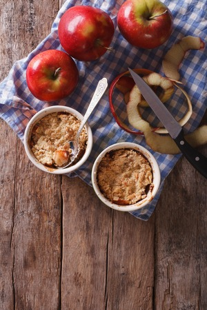 apple crumble: apple crumble in portion pots on the table. vertical top view of rustic style