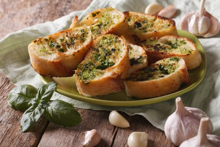 crusty french bread: Toasts with basil and garlic close-up on a plate. horizontal, rustic style