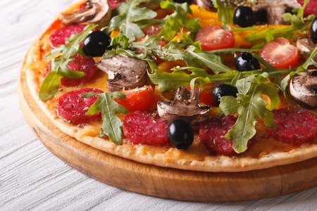 italy food: Delicious pizza with herbs, vegetables and salami close up on the table. horizontal