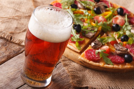 arugula: Cold beer and hot pizza with arugula on the table close-up horizontal. rustic style
