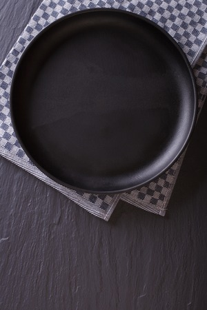 plate setting: Tableware: black empty plate on the table. top view vertical Stock Photo