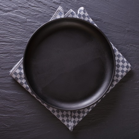 napkin: Tableware: black empty plate on the table. top view