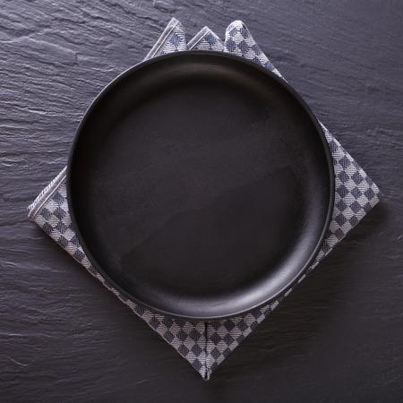napkin: Vajilla: plato vacío negro sobre la mesa. vista superior Foto de archivo