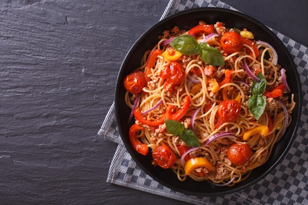 Beautiful spaghetti with minced meat and vegetables on a plate. horizontal view from above