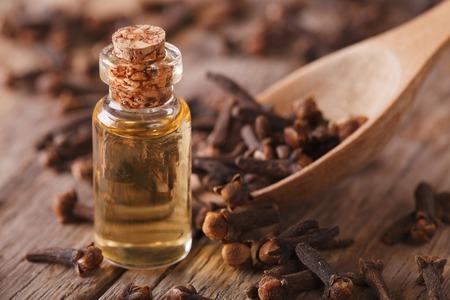 oleos: el aceite de clavo en una botella de vidrio en primer plano en la mesa. horizontal Foto de archivo