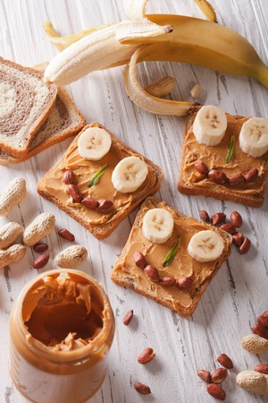 children breakfast: Sandwiches for children with peanut butter and banana on the table. Vertical view from above