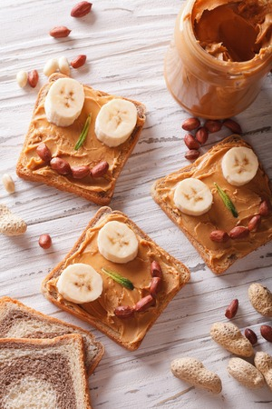 food allergies: Kids sandwiches with peanut cream and banana. top view vertical