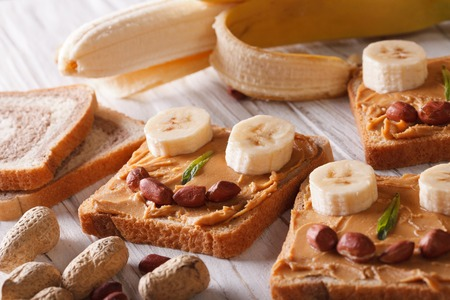 sandwich spread: Funny sandwiches with peanut butter and banana on the table. horizontal Stock Photo