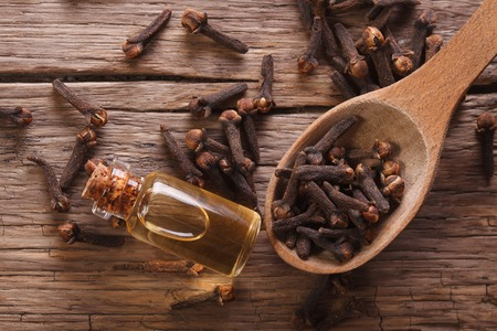 The essence of cloves in the bottle macro on the table. horizontal view from above