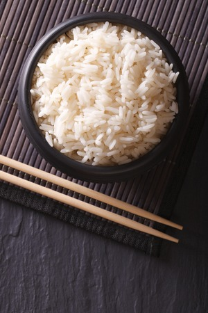 cooked rice: Dietary rice in a black bowl close-up and chopsticks. vertical top view