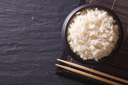arroz blanco: Comida japonesa: el arroz en un tazón negro y palillos. visión horizontal desde arriba