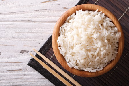 Japanese food: steamed rice in a wooden bowl and chopsticks. horizontal view from above