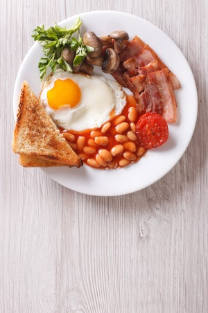 beans on toast: English breakfast: fried egg, bacon, beans and toast on a plate close-up