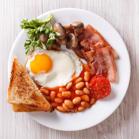 british foods: English breakfast: fried egg, bacon, beans and toast on a plate close-up
