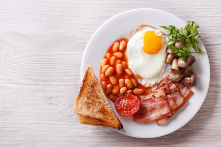 bacon fat: Fried egg with bacon, beans and toast on a plate Stock Photo