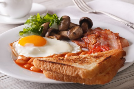 bacon baked beans: English breakfast: fried eggs with bacon and vegetables close-up on a plate