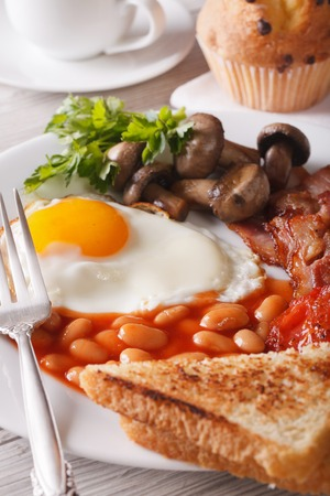 bacon baked beans: Traditional English breakfast: eggs with bacon and vegetables close-up on a plate. Vertical