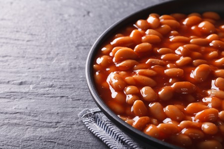 beans in tomato sauce in a black bowl close-up horizontal Stock Photo