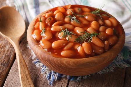 alubias: alubias blancas en salsa de tomate en un tazón de madera Foto de archivo