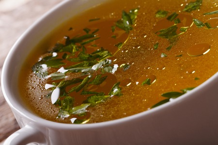 Tasty meat broth with parsley in white bowl close-up. horizontal