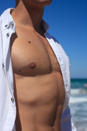 muscle shirt: Male torso closeup on a background of blue sky and water