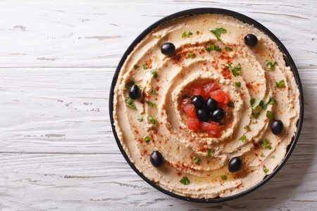 lebanese food: Fresh hummus with olives, tomatoes and herbs on a plate