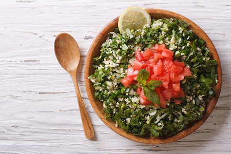 Tabbouleh salad in a wooden bowl on the table