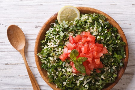 traditional food: Tabbouleh salad closeup in a wooden bowl on the table Stock Photo