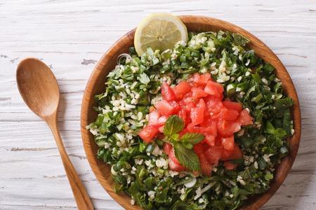 comida arabe: Tabulé ensalada de cerca en un cuenco de madera sobre la mesa Foto de archivo