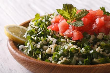 tabbouleh: Fresh Tabbouleh salad closeup in a wooden bowl